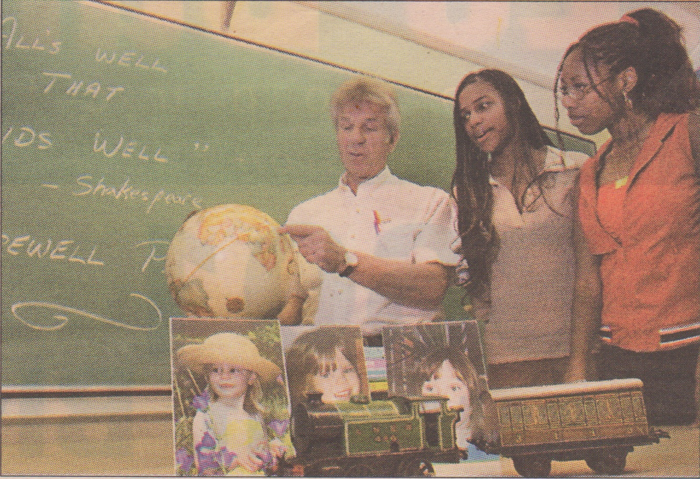 RICHARD ARLESS JR. THE GAZETTE English teacher Chris Eustace retires this month. He shows Pierrefonds Com-prehensive High School Grade 10 students Chandecia Walker (centre) and Vanessa Bryan where he was born in Africa.